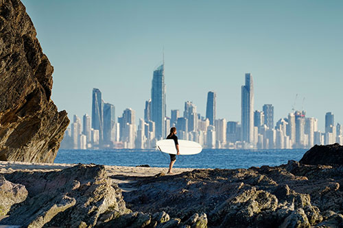 Surfer on rocks at Gold Coast.